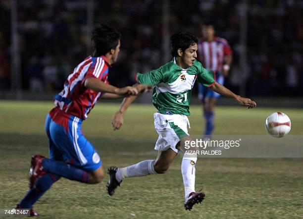 Jhasmani Campos de la seleccion de Bolivia se lleva el balon ante la marca de Julio Caseres de Paraguay durante un partido amistoso el 20 de junio de...