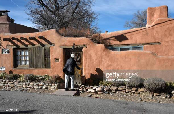 Santa Fe New Mexico resident enters the front door of her historic adobe home