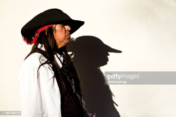 santa fe, nm: native american man walks by sunny white wall - handsome native american men stock pictures, royalty-free photos & images