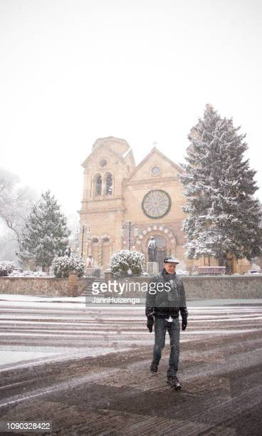 santa fe, nm: saint francis kathedrale in schnee, fußgänger - francis winter stock-fotos und bilder