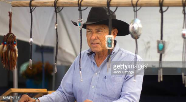 santa fe, nm, usa: man in booth sells bolo ties at fiesta - handsome native american men stock pictures, royalty-free photos & images