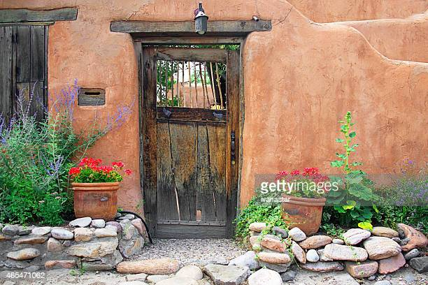 Santa Fe Stucco Wall, Wooden Gate and Flowers