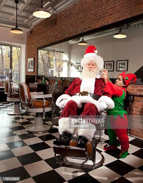 Santa getting haircut from elf