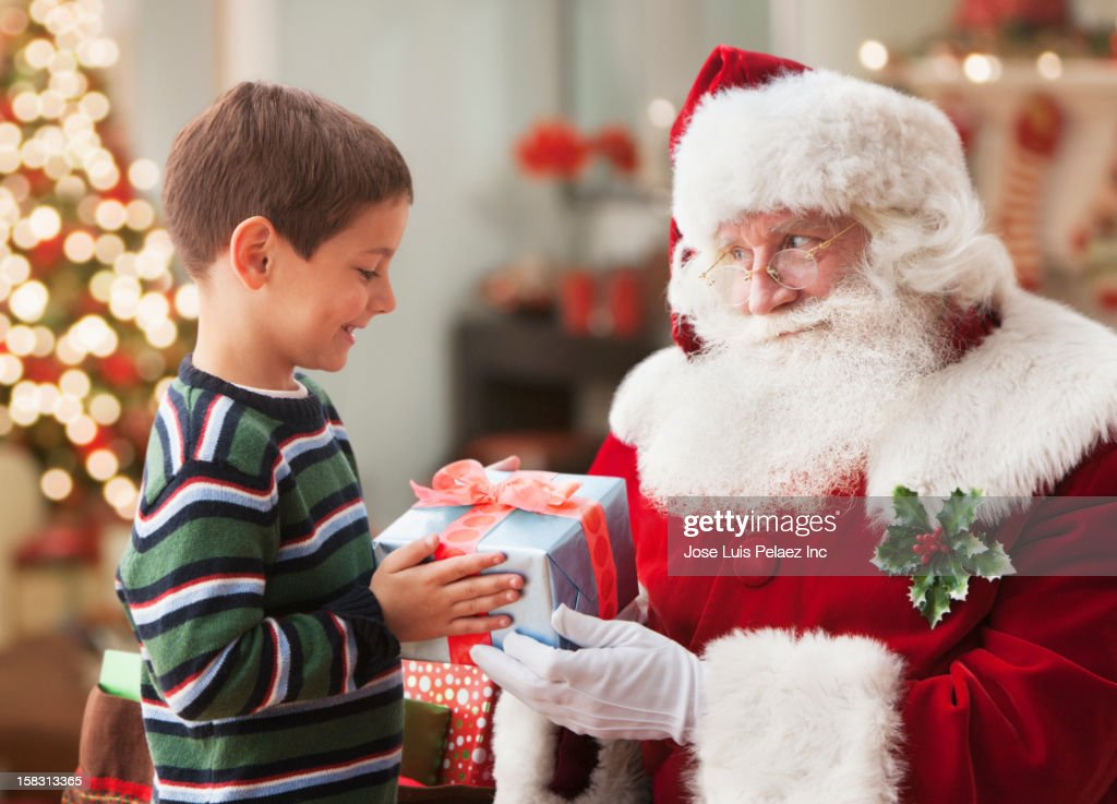 Santa giving Caucasian boy Christmas gift : ストックフォト