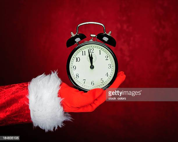 santa hand holding vintage clock