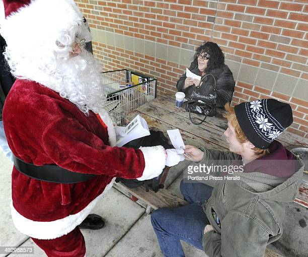 Santa hands out bills to Rachael Nicholas from Westbrook and Thomas Verow from Portland as the Secret Santa got off a Metro bus in Westbrook from...