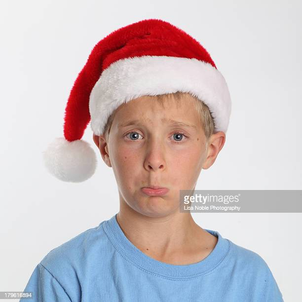 Santa Hat - Boy pouting while wearing Santa Hat