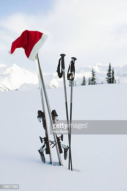 Santa hat hanging from skis planted in snow in mountain landscape