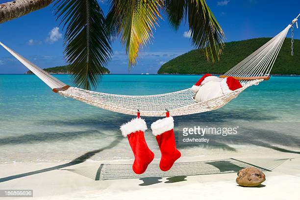santa hats and stocking at a tropical caribbean beach - caribbean christmas stock pictures, royalty-free photos & images