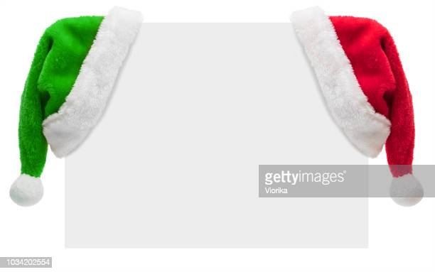 santa hats on a blank placard with copy space (isolated on white) - christmas banner stock photos and pictures