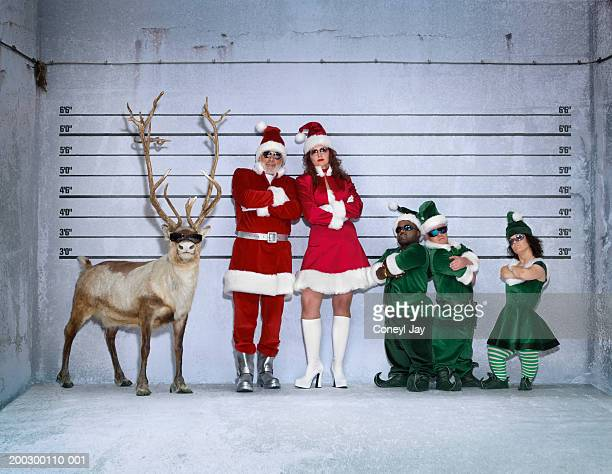 Santa, helper, elves and reindeer in police identity parade, portrait