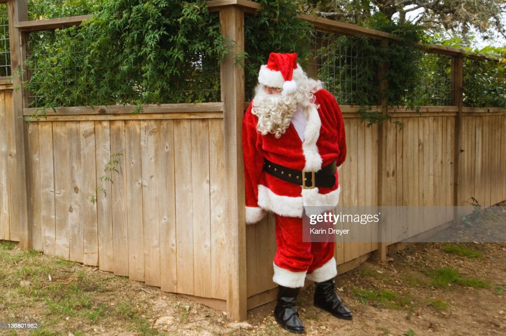 Santa hiding behind fence : Stock Photo