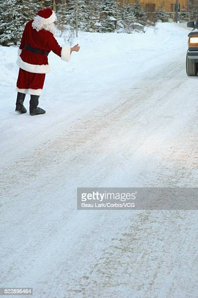 santa hitchhiking on snowy road - pere noel voiture photos et images de collection