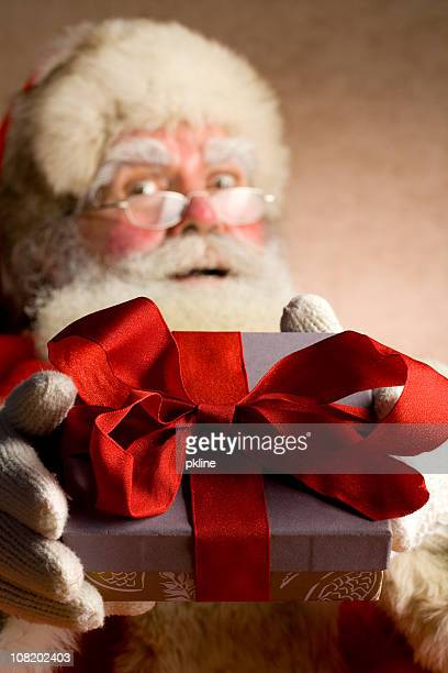 Santa holds a gift box toward the camera