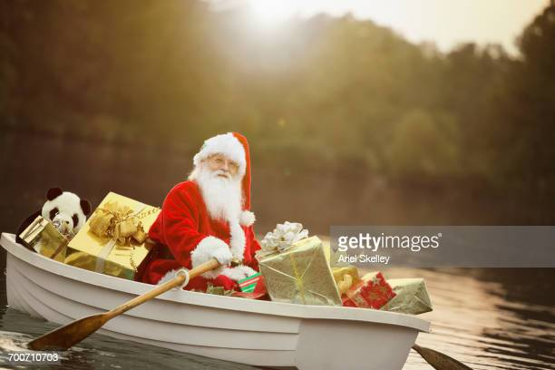 santa in rowboat with christmas gifts - mere noel stock pictures, royalty-free photos & images
