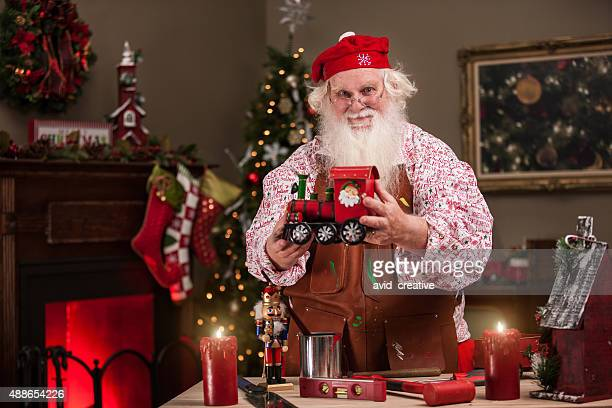santa in workshop showing a toy train - santas workshop stock photos and pictures