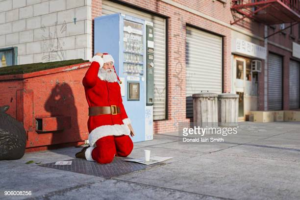 Santa kneeling on sidewalk begging