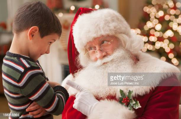 santa lecturing caucasian boy - naughty santa stock photos and pictures