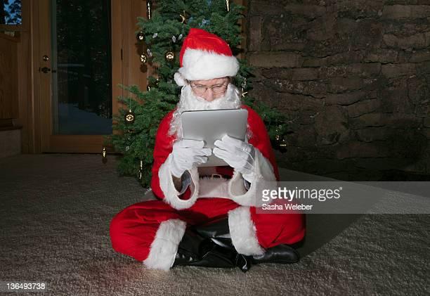 Santa looking at Tablet Under Christmas Tree