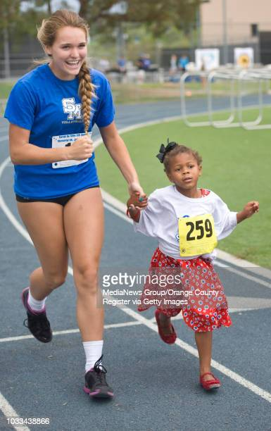 Santa Margarita Catholic High School volleyball player Claire Archibald keeps 4yearold Savvy Johnson company during the kids fun run at the Sarah...