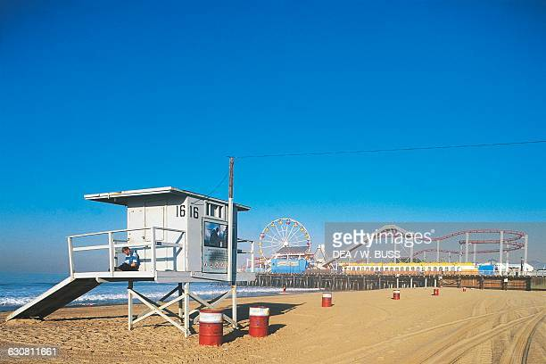 Santa Monica beach with the control tower and an amusement park with roller coasters Los Angeles California United States of America