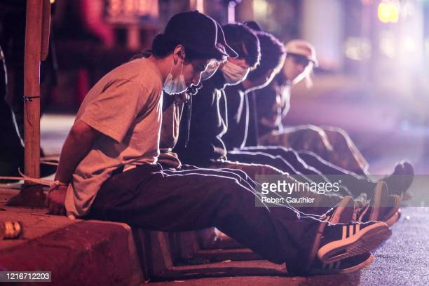 Santa Monica, CA, Sunday May 31, 2020 - Suspected looters sit handcuffed on Santa Monica Blvd. After being spotted running from a CVS store nearby.