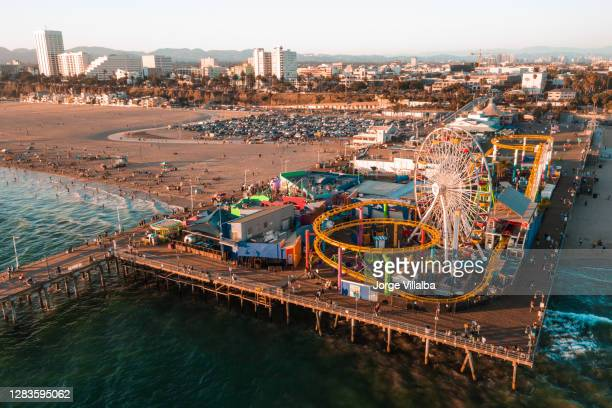 santa monica pier at sundown with lights reflected in the pacific ocean - santa monica pier stock pictures, royalty-free photos & images