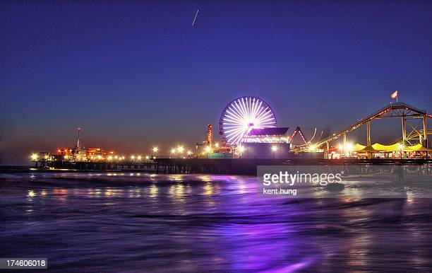 Santa Monica pier with colorful Ferris wheel and lights. Beautiful light reflection upon ocean waves with star trail in the sky.