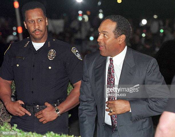 Santa Monica police officer looks on 04 February as defendant O.J. Simpson arrives at the Santa Monica Courthouse where he was found liable in the...