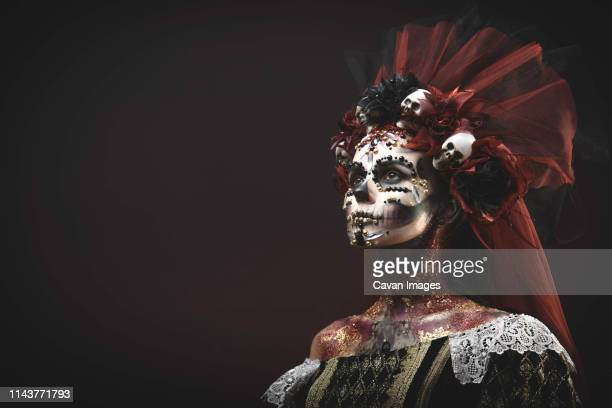 santa muerte young girl with artistic halloween makeup and with sculls - body paint stock pictures, royalty-free photos & images