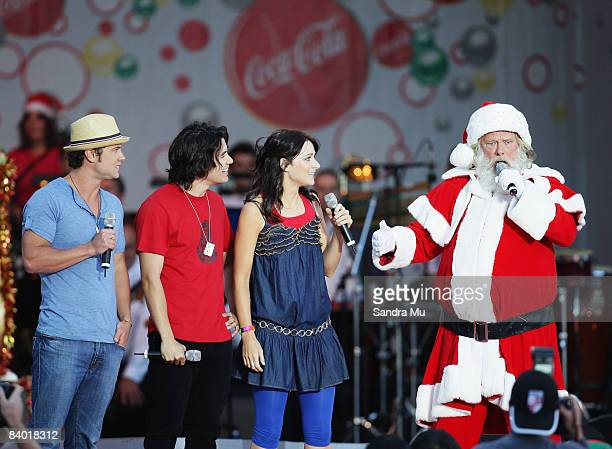Santa performs live on stage with Sticky TV presenters Sam Wallace Drew Neemia and Erin Simpson during CocaCola Christmas In The Park at Auckland...