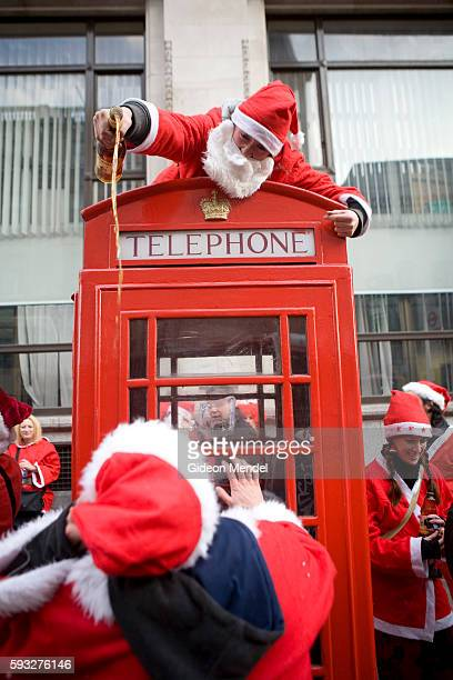 A Santa pours brandy from the top of a telephone box into the mouths of other eager Santas during the London SantaCon event SantaCon is a mass...
