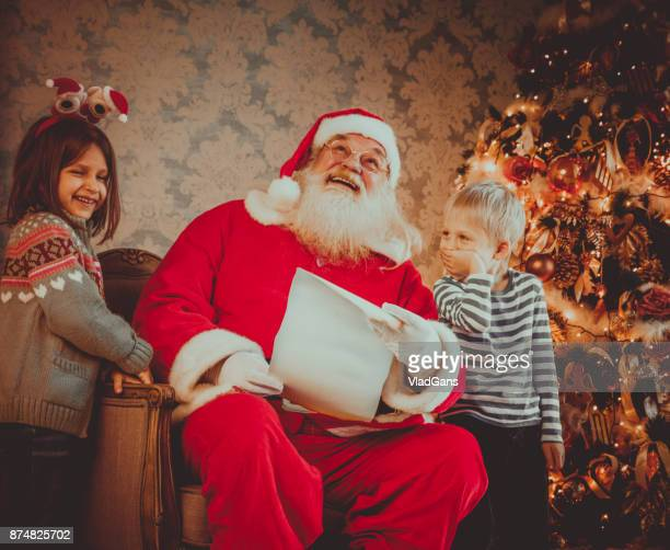 Santa reading Christmas letter with kids