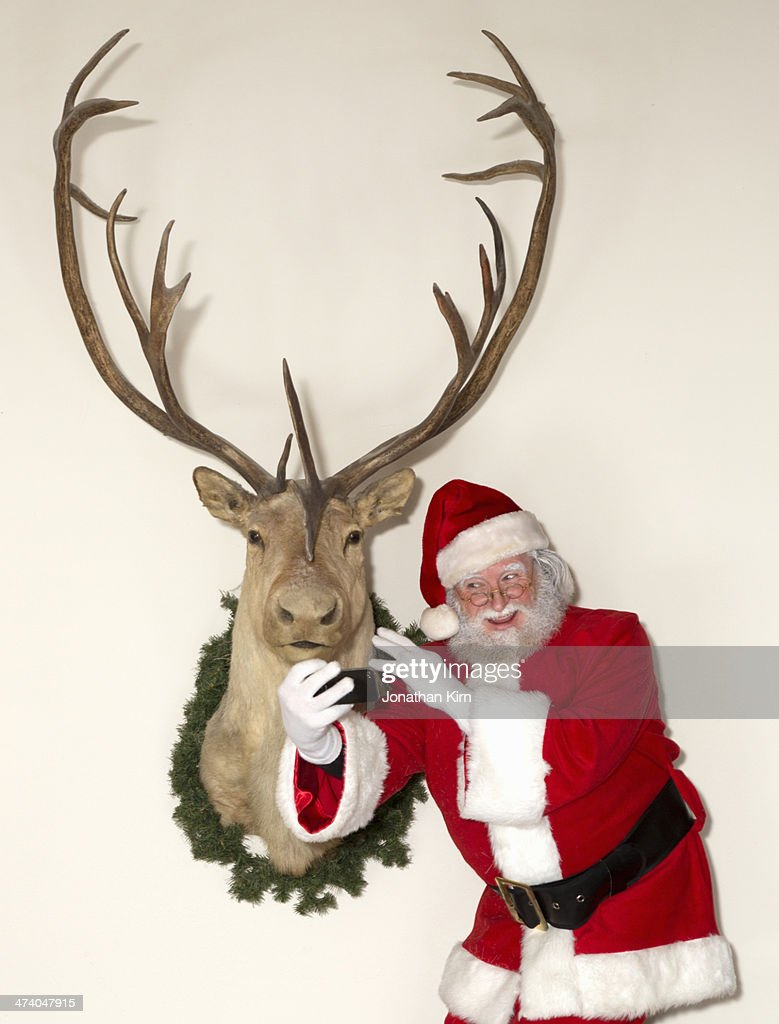 Santa shoots a selfie with a reindeer : Stock Photo