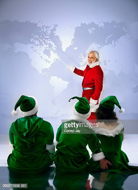 'santa' showing three 'elves' world map (digital composite) - women groping men stock pictures, royalty-free photos & images