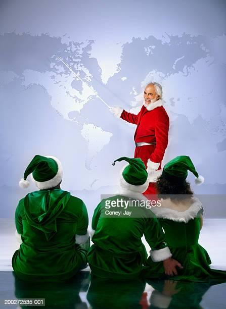 'Santa' showing three 'elves' world map (digital composite)