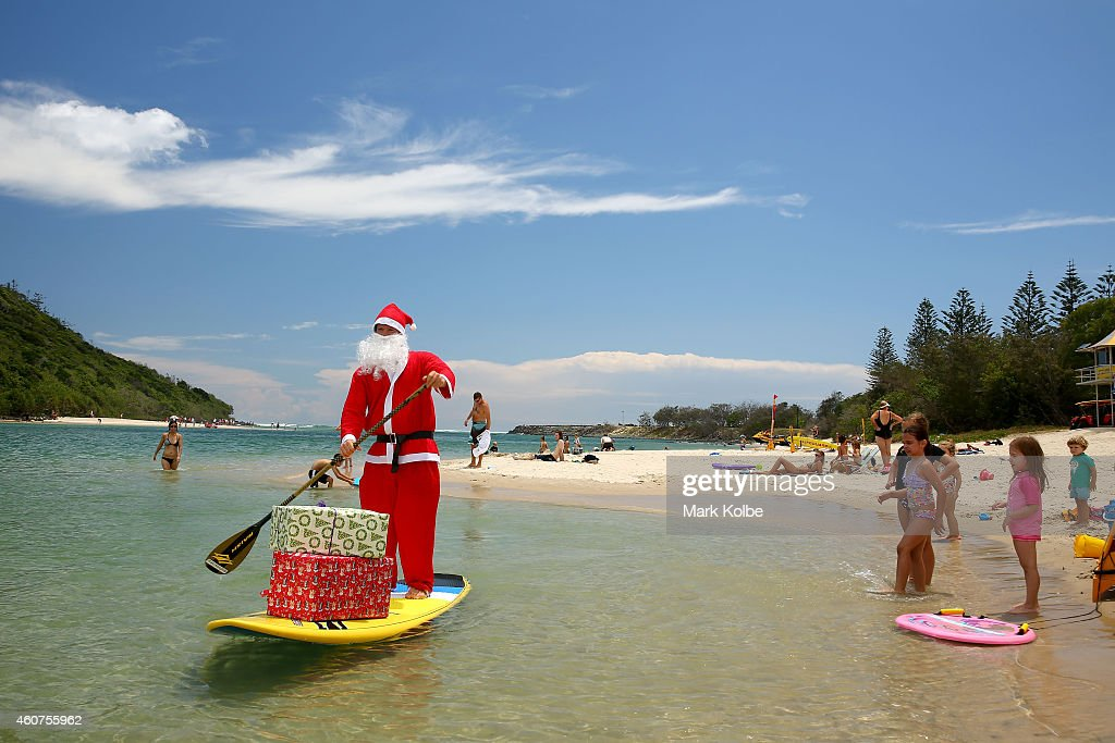 Santa swaps his sleigh for a Stand Up Paddle board to deliver presents to children at Tallebudgera Creek on December 9, 2014 on the Gold Coast in Queensland, Australia. Queensland's beaches rank amongst the best in the world and Christmas in Queensland is about sun and summer. You'll find the warmest, whitest, biggest and most beautiful beaches stretched along the 7,400km coastline of Queensland, Australia.