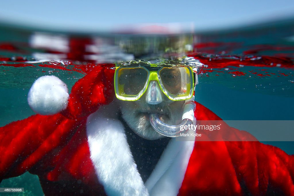 Santa takes a dip in the waters of Australias Great Barrier Reef Marine Park to cool off. Christmas in Queensland is celebrated in summer and has temperatures in the comfortable 20s-30s (celsius). The Great Barrier Reef in Queensland Australia is the largest and most extensive coral reef system in the world comprising about 2,900 individual coral reefs, 600 continental islands and 300 coral cays. The Great Barrier Reef is the largest natural feature on earth and its impressive size makes it the only living structure that can be seen from the moon. The Great Barrier Reef is 2,300 kms long and approximately 350 000 kms? in size. Thats about 70 million football fields, or the size of Japan!