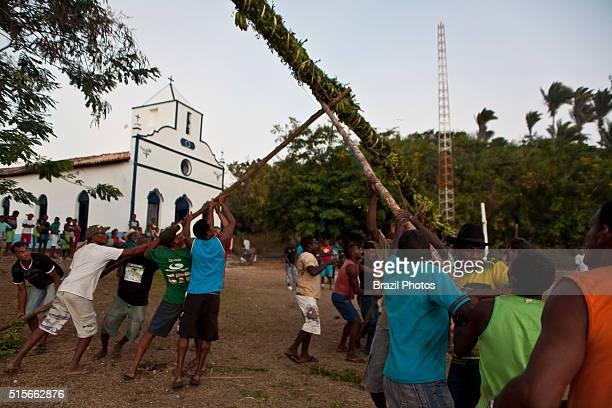 Santa Teresa D´Avila celebration at Itamatatiua Quilombo Alcantara Maranhao State northeastern Brazil Men raise up a heavy decorated trunck that will...