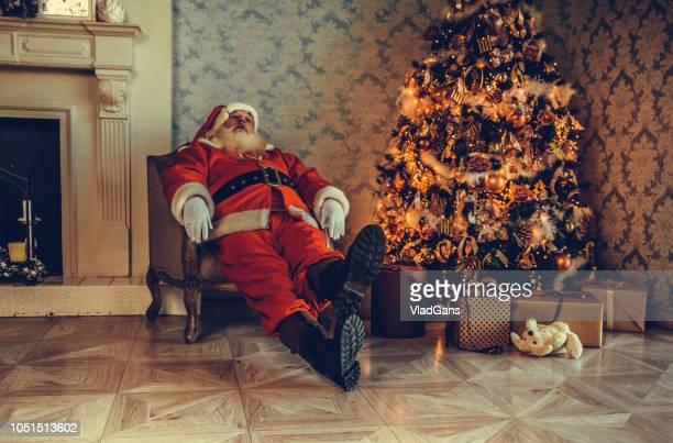 Santa tired asleep near Christmas tree
