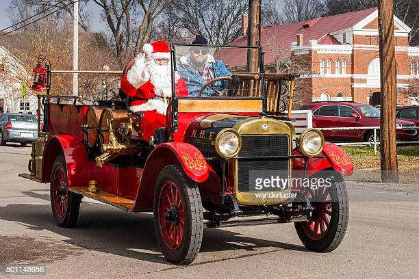Santa waves from a vintage firetruck
