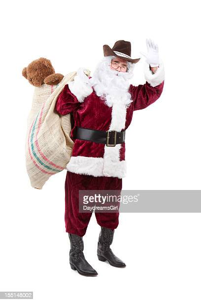 santa wearing cowboy hat and boots with burlap toy sack - cowboy christmas stock pictures, royalty-free photos & images