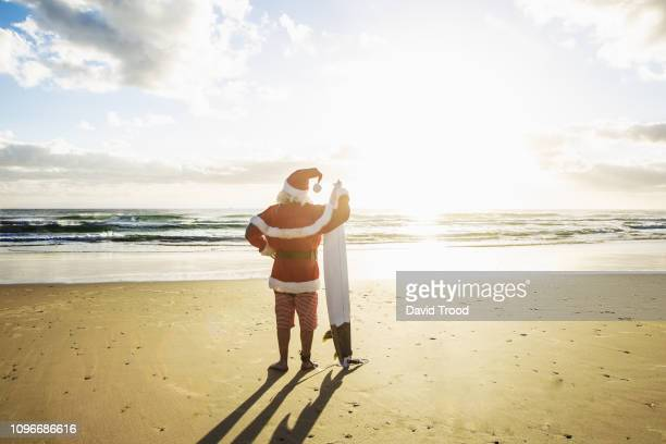santa with surfboard. - beach christmas stock pictures, royalty-free photos & images