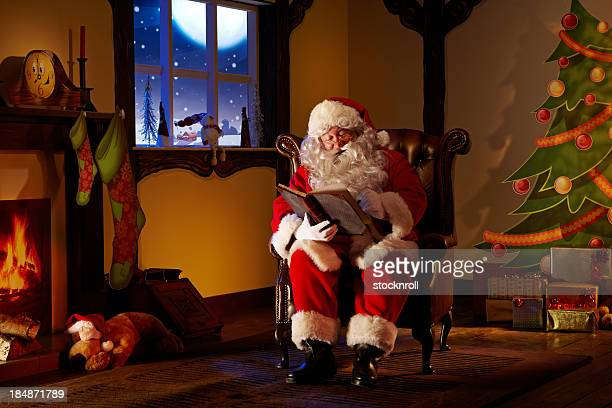 Santa writing in a book.