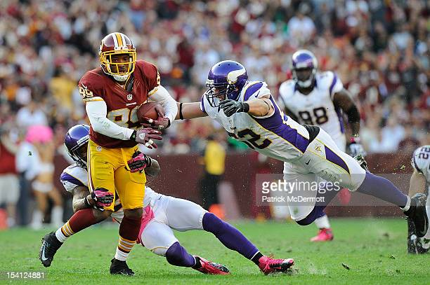 Santana Moss of the Washington Redskins is tackled by Chris Cook and Chad Greenway of the Minnesota Vikings in the first half of a game at FedExField...