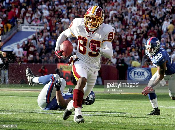 Santana Moss of the Washington Redskins runs the ball toward the end zone for his first touchdown against the New York Giants during the first half...