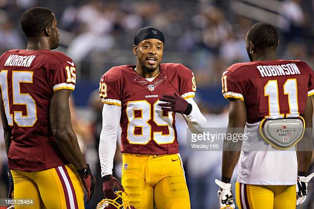 Santana Moss talks with Aldrick Robinson and Joshua Morgan of the Washington Redskins before a game against the Dallas Cowboys at ATT Stadium on...