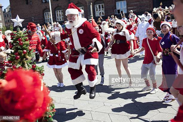Santas dance around a Christmas tree at town hall square in Copenhagen on July 21 2014 during the Santas parade AFP PHOTO / Scanpix / David Leth...