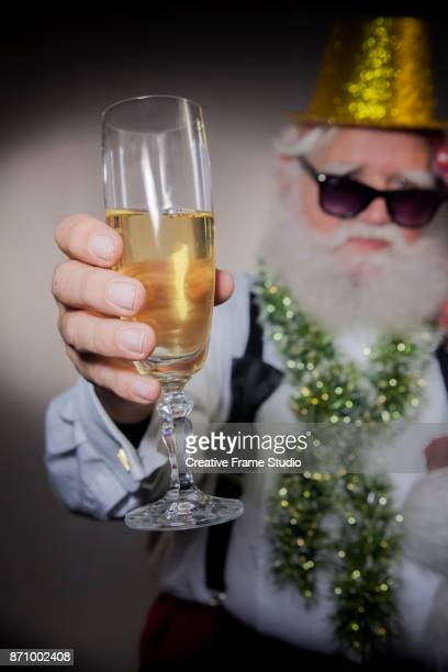 Santa's hand holding a glass of champagne on a celebration