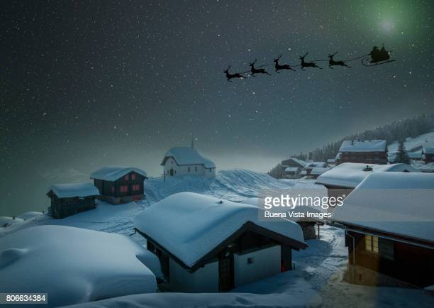 santa's sledge in a starry sky over a village in the snow - rentier stock-fotos und bilder